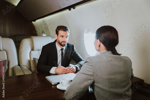 Valokuvatapetti Businessman Talking With Secretary While Sitting In Privet Jet