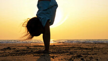 Girl Doing Handstand At Beach During Sunset