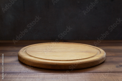 Obraz pizza cutting board at wooden table - fototapety do salonu