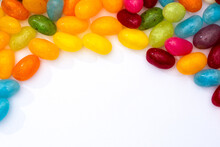 Bright Colorful Photograph Of Candy Jelly Beans Shot From Above On A White Background With Copy Space
