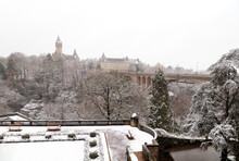 Snowfall In Luxembourg With A View On The BCEE Clock Tower Of Spuerkees Bank And The Adolphe Bridge In Luxembourg City