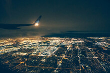 Airplane Flying Over Illuminated Cityscape Against Sky At Night