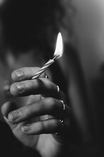 Grayscale Shallow Focus Shot Of A Female Hand Holding A Lit Birthday Candle As A Cigarette