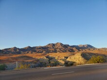 Scenic View Of Road And Mountains Against Clear Blue Sky