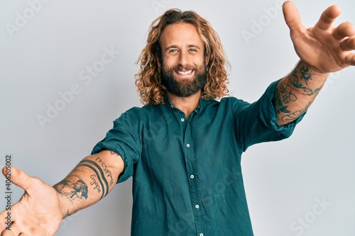 Fotografia, Obraz Handsome man with beard and long hair wearing casual clothes looking at the camera smiling with open arms for hug