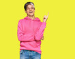 canvas print picture - Young hispanic man wearing casual pink sweatshirt with a big smile on face, pointing with hand and finger to the side looking at the camera.
