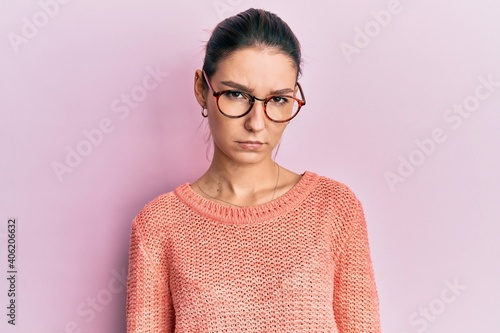 Fototapeta Young caucasian woman wearing casual clothes and glasses skeptic and nervous, frowning upset because of problem