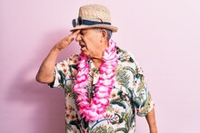 Senior Handsome Grey-haired Man On Vacation, Wearing Summer Look With Hawaiian Lei Flowers Surprised With Hand On Head For Mistake, Remember Error. Forgot, Bad Memory Concept.