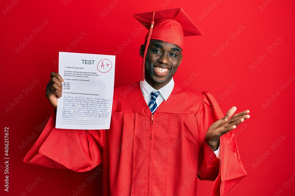 Fototapeta Young african american man wearing graduation cap and ceremony robe showing passed exam celebrating achievement with happy smile and winner expression with raised hand