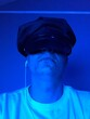 Leinwandbild Motiv Close-up Of Man Wearing Cap And Headphones In Blue Light