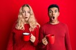 Leinwandbild Motiv Young interracial couple holding coffee scared and amazed with open mouth for surprise, disbelief face