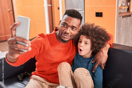 Fotografie, Obraz Father making self-portrait with his son while sitting at sofa