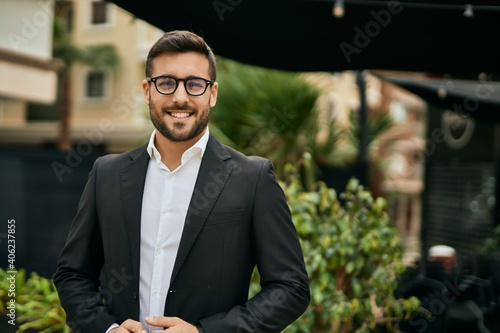 Fototapeta Young hispanic businessman smiling happy standing at the city. obraz