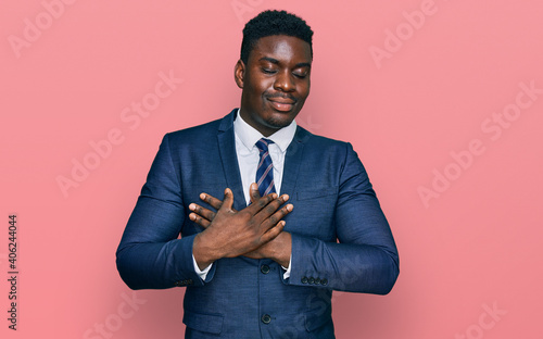 Canvas Print Handsome business black man wearing business suit and tie smiling with hands on chest with closed eyes and grateful gesture on face