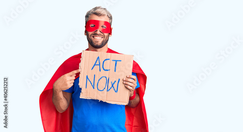 Young blond man wearing super hero costume holding act now cardboard banner smil Wallpaper Mural