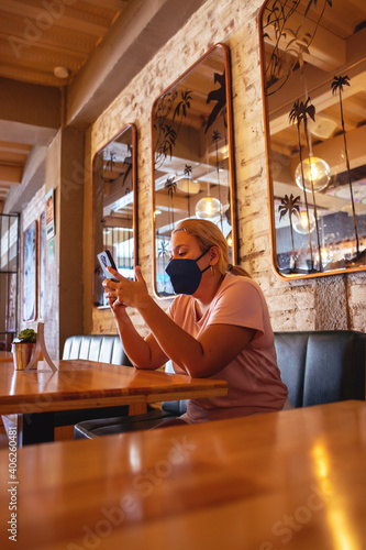 woman in restaurant calling on the phone while reading restaurant menu card wear фототапет