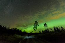 Man Standing On Road Watching Aurora