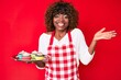 Leinwandbild Motiv Young african american woman wearing apron holding cupcake celebrating achievement with happy smile and winner expression with raised hand