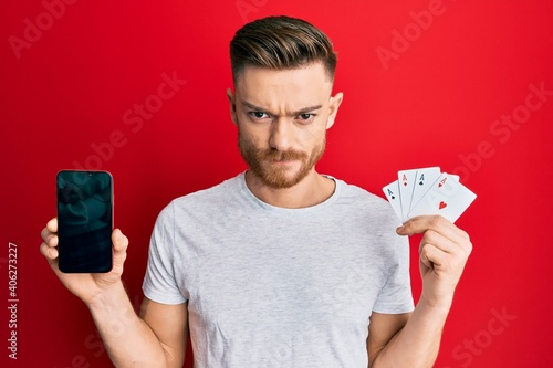 Fotografie, Obraz Young redhead man holding smartphone and casino card skeptic and nervous, frowning upset because of problem