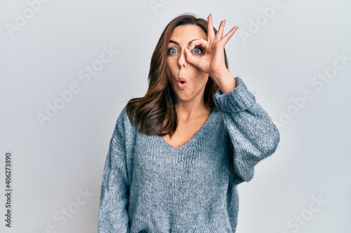 Fotografie, Obraz Young brunette woman wearing casual winter sweater doing ok gesture shocked with surprised face, eye looking through fingers