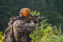 Young Hunter Aiming Rifle In The Forest