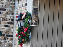 Downy Woodpecker Eating From A Bird Feeder In Front Of A Christmas Wreath: A Christmas Visitor Of A Downy Woodpecker Bird To A Bird Feeder With A Christmas Wreath In The Background