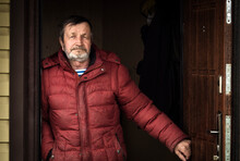 An Elderly Man In A Jacket On The Doorstep Of His House