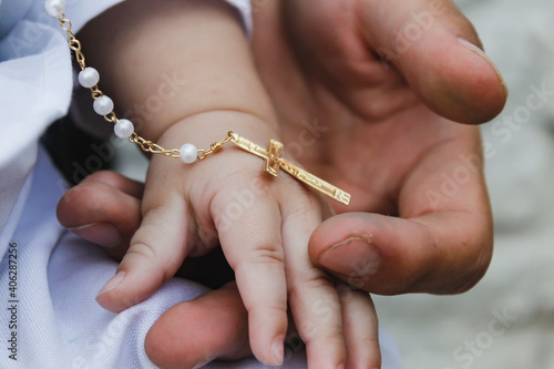 Man's hand holding the hand of a baby, on the day of his christening and with a medal of the cross Fotobehang