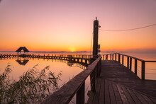 A Beautiful View Of A Wooden Dock Over The Sea Under The Breathtaking Sunset Sky