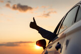 Man On Car Against Orange Sky During Sunset
