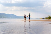 A Beautiful Mature Couple Walks Along The Wild Beach Holding Hands Against The Background Of The Volga Open Spaces And The Zhiguli Mountains On A Summer Day