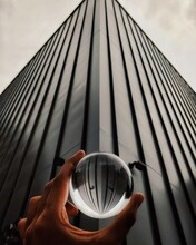 Cropped Hand Holding Crystal Ball Against Building