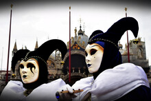 Two Joker Costumed Masquerades At The Carnival Of Venice With St Mark's Basilica In The Background