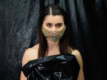 Pandemic Fashion Art. Costume Party. Glamour Look. Mysterious Woman In Handmade Gold Chain Face Mask Black Polyethylene Dress Isolated On Dark Wrinkled Texture Background.