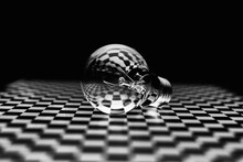 An Abstract Image Of An Incandescent Lamp On A Black-and-white Checkered Surface.