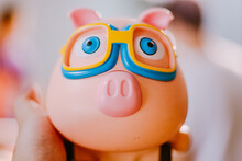 Close-up Of Piggy Bank Held By Human Hand