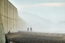 People Walking At Beach Against Foggy Morning