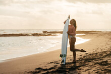Young Attractive Surfer Woman With White Board At Sunset On The Ocean. Bali Indonesia. Summer Time, Sports, Travel Content.