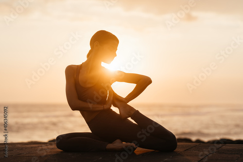 Obraz Yoga at sunset on the beach. woman performing asanas and enjoying life on the ocean. Bali Indonesia. - fototapety do salonu