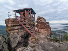 Tourist Shelter Or Hut On Rock By Misty Valley Against Sky