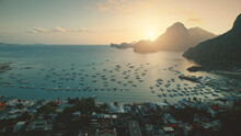 Aerial Sunset At Ocean Harbor With Boats Of Tropic Port Town Cityscape. Buildings, Lodges, Homes With Resort At Sand Coast. Mount Philippines Island Silhouette At Sun Light. Cinematic Drone Shot