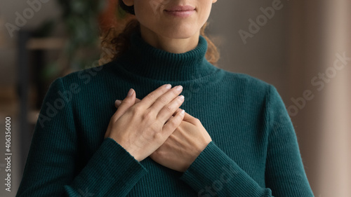 Foto Crop close up of Caucasian woman hold hands in prayer at heart chest feel religious superstitious