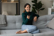 Leinwandbild Motiv Overjoyed millennial Caucasian woman sit relax on sofa in living room enjoy cozy domestic weekend. Happy young 20s female rest on couch at home laugh watching TV program. Entertainment concept.