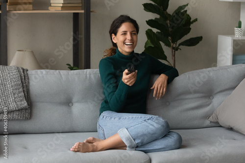 Obraz Overjoyed millennial Caucasian woman sit relax on sofa in living room enjoy cozy domestic weekend. Happy young 20s female rest on couch at home laugh watching TV program. Entertainment concept. - fototapety do salonu