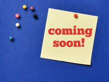 Text COMING SOON Written On Yellow Paper Note With Pin Board Over Blue Background.Business Concept.
