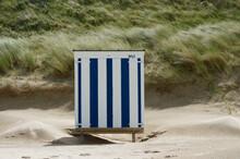 Striped Beach Hut On Beach Against Grass