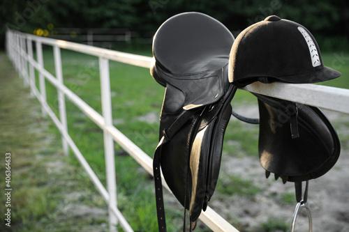 Skórzane siodło konia i kask na drewnianym płocie na zewnątrz