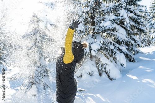 Happy woman throwing snow in the air at sunny winter day. Enjoying Winter. © Daniel Jędzura