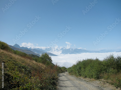 Russia, North Ossetia. The road to the Fiagdon relay. Mountain road among the greenery. Clouds below the snow-capped mountains.