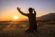 Man With Hands Raised In The Sunset